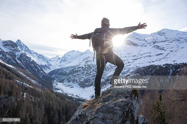 Hiker stretches arms to sunrise, mountains