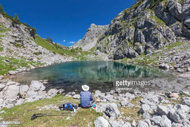 Hiker take a break in the Mountains at Lake Seeleinsee in Nationalpark Berchtesgaden