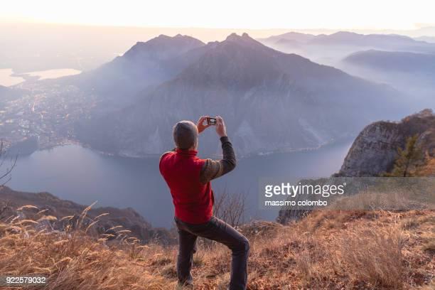 hiker take a pic on mountain - chum stock-fotos und bilder