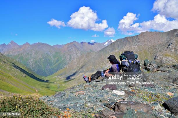 a hiker takes a rest on top of a mountain - kyrgyzstan stock pictures, royalty-free photos & images