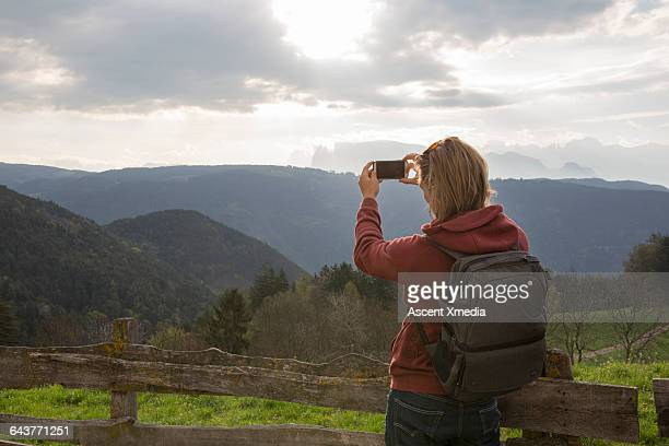 hiker takes pic of mountain scene from rural fence - mid length hair stock pictures, royalty-free photos & images