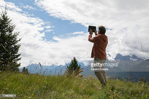 Hiker takes picture from mountain meadow