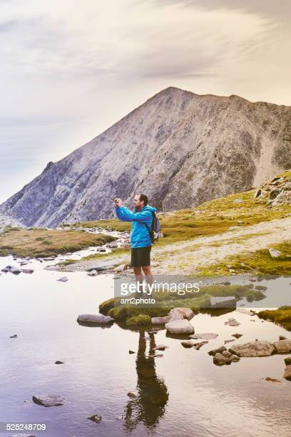 Hiker takes picture from river above mountains