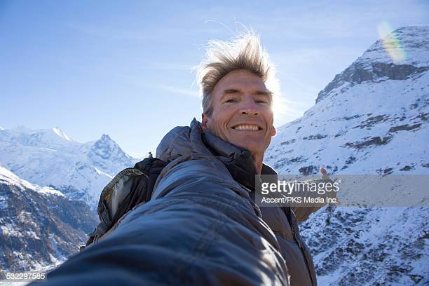 Hiker takes selfie portrait, in snowy mountains