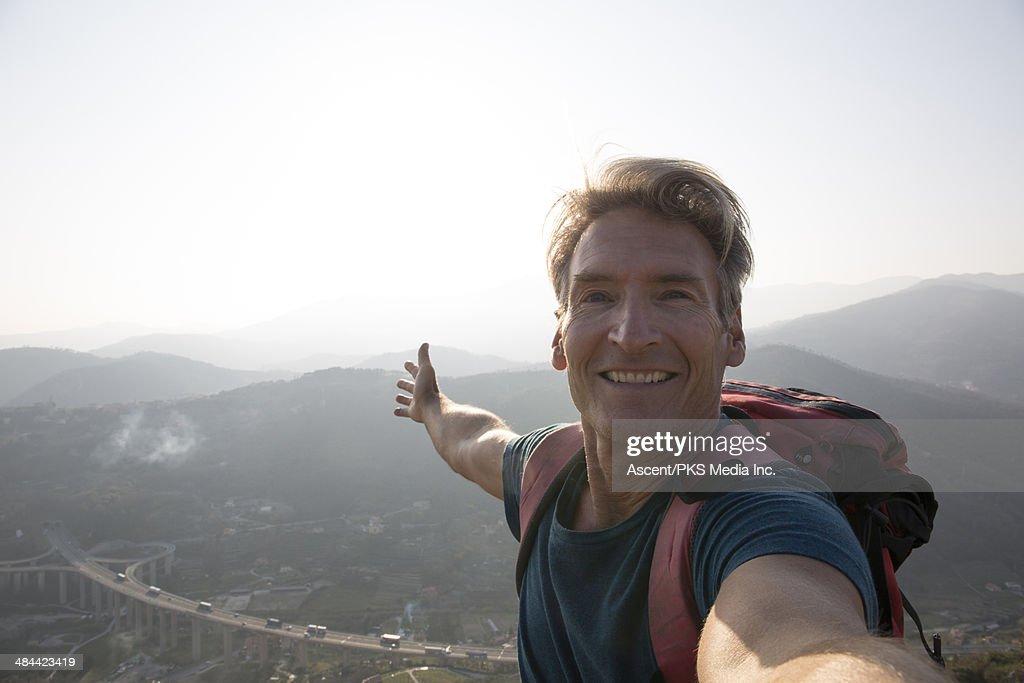 Hiker takes selfie portrait on mountain top : Stock Photo