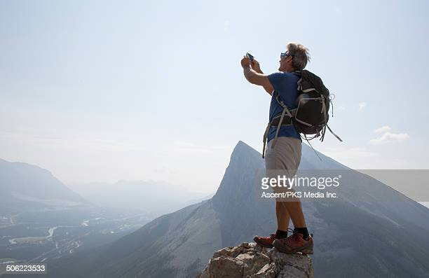 Hiker takes smart phone pic from mountain summit