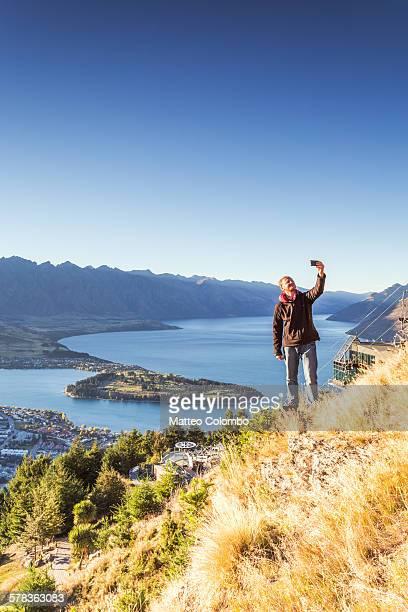 Hiker taking a selfie from lookout, Queenstown