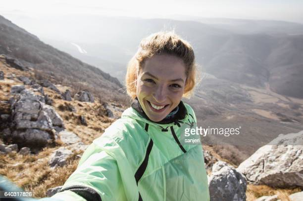 hiker taking a selfie on the top of the hill - one young woman only stock pictures, royalty-free photos & images