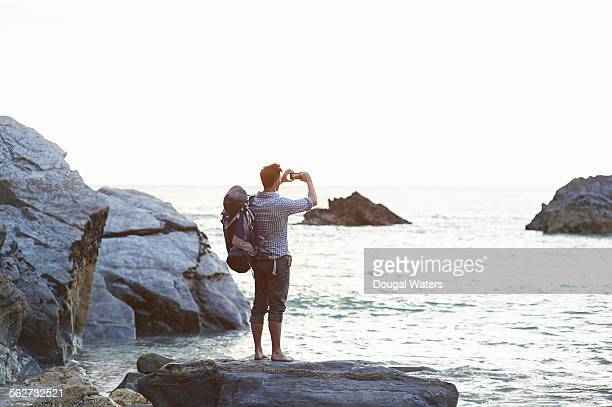 Hiker taking photo of sea with camera phone
