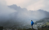 Hiker traveler in foggy mountains
