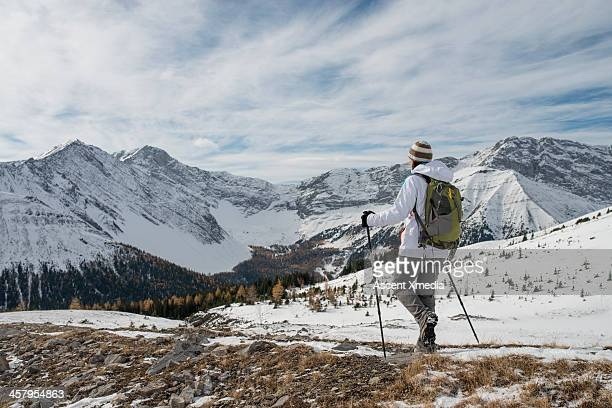 Hiker traverses snow covered landscape, mountains