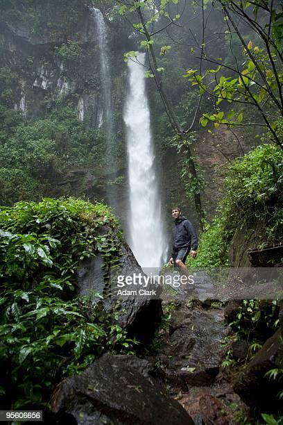 A hiker under a jungle waterfall in Costa Rica.