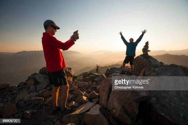 A hiker uses a tablet to take a picture of his friend standing next to the summit cairn of Sauk Mountain.