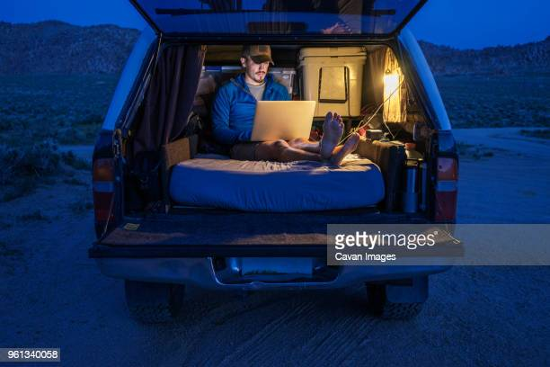 hiker using laptop in car trunk during vacation - remote location stock pictures, royalty-free photos & images