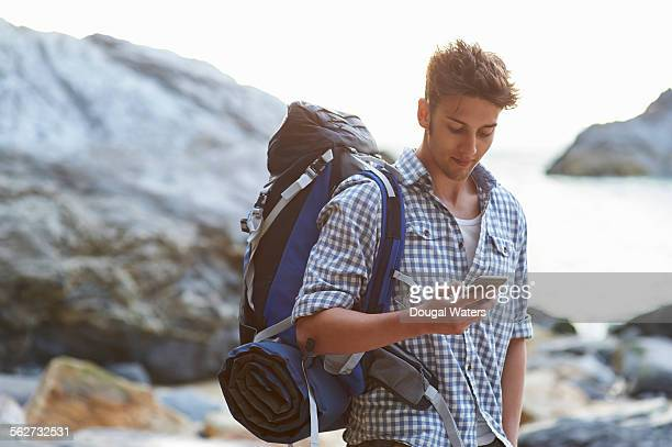 hiker using mobile phone on rocky beach - rucksacktourist stock-fotos und bilder