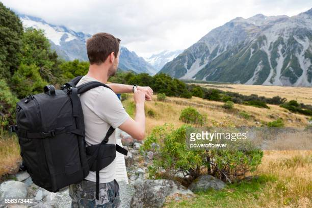 Hiker using Smart Watch at Mount Cook of the Southern Alps in New Zealand