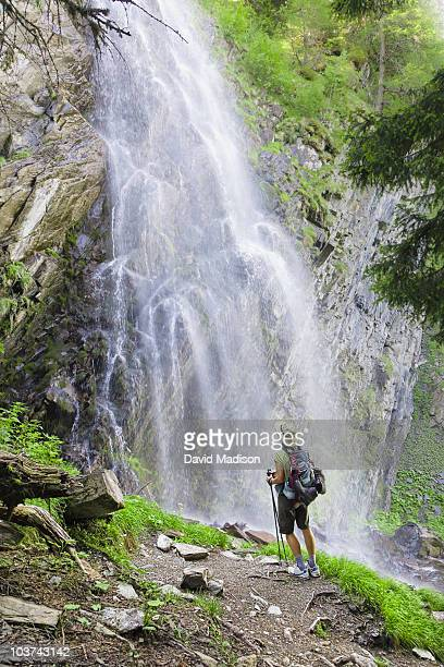 Hiker viewing waterfall on Mont Blanc circuit.
