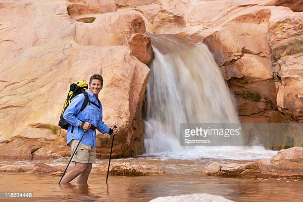 hiker wading in water at bottom of waterfall - capitol reef national park stock pictures, royalty-free photos & images
