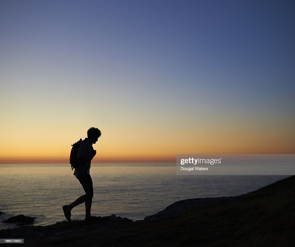 Hiker walking along coastline at sunset. : Stock Photo