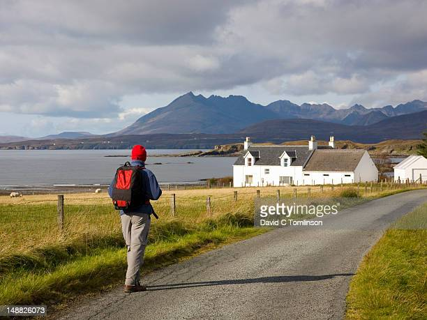 Hiker walking along country lane near Tarskavaig towards Cuillin hills with whitewashed house prominent, Sleat Peninsula.