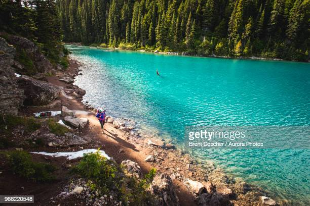 hiker walking along lakeshore, british columbia, canada - garibaldi park stock pictures, royalty-free photos & images
