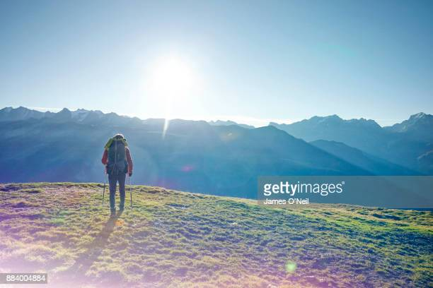 Hiker walking away in mountain range, Switzerland