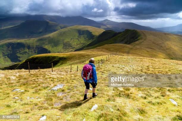 Hiker walking down from Moel Eilio towards Snowdon in Snowdonia