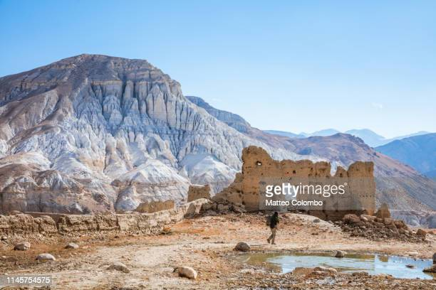 hiker walking near old ruins, lo manthang, upper mustang region, nepal - lo manthang stock pictures, royalty-free photos & images