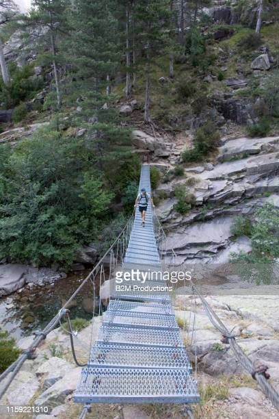 hiker walking on bridge in corsica - 2010 2019 stock pictures, royalty-free photos & images