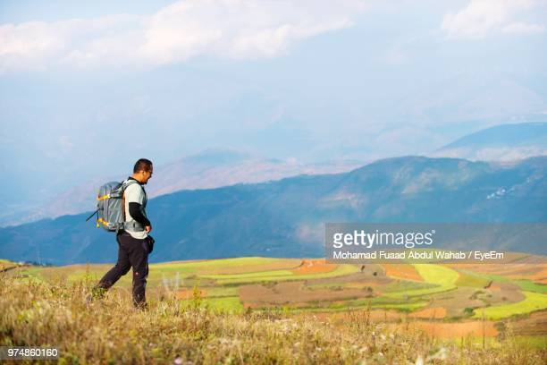 Hiker Walking On Field Against Mountain Range