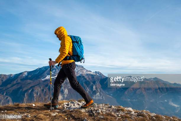 hiker walking on high path mountain - yellow coat stock pictures, royalty-free photos & images