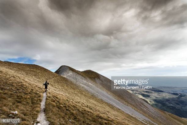 Hiker Walking On Mountain Against Cloudy Sky