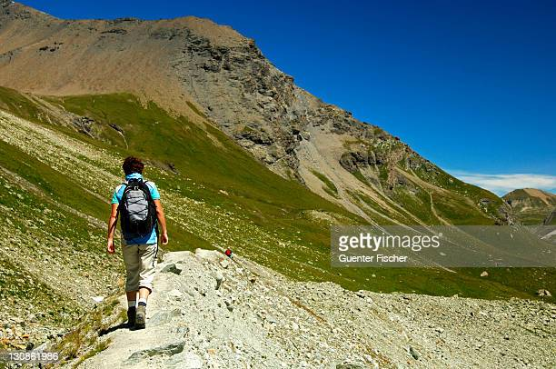 hiker walking on the narrow ridge of the lateral moraine of the moiry glacier, pennine alps, valais, switzerland, europe - vista lateral stock pictures, royalty-free photos & images