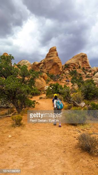 hiker walking towards rock formations against sky - florin seitan stock pictures, royalty-free photos & images
