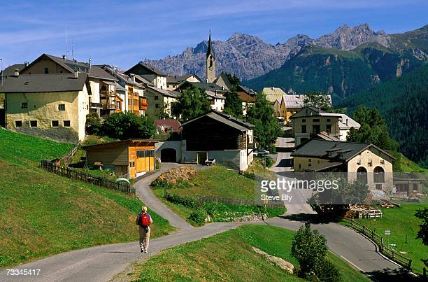 hiker walking towards small mountain village of guarda, lower engadine valley, switzerland - guarda switzerland stock pictures, royalty-free photos & images