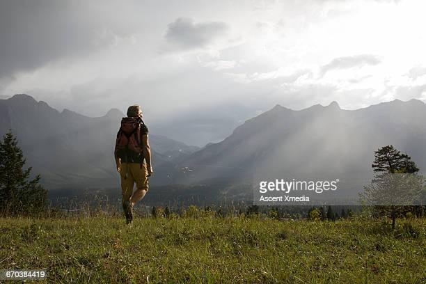 Hiker walks across meadow, light rays over mtns