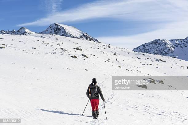 Hiker walks on snowy mountain