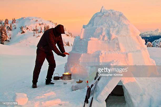 Hiker warms his hands above stove
