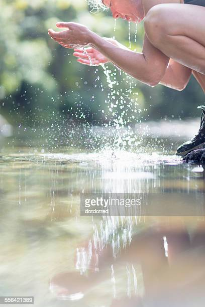 Hiker washing face with water from shallow stream