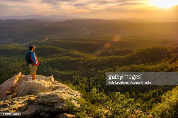 hiker watches sunrise on edge of cliff above valley - weitwinkelaufnahme stock-fotos und bilder