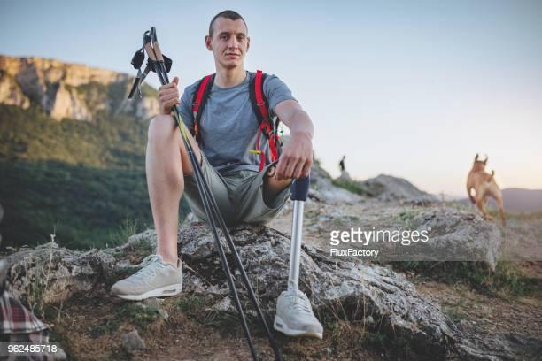 hiker with artificial limb hiking with his dog - pessoas com deficiência imagens e fotografias de stock