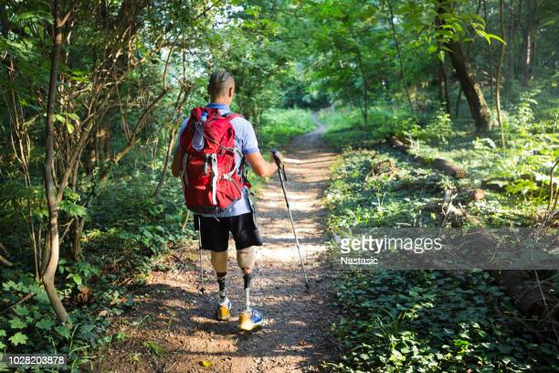 Hiker with artificial limbs hiking in nature