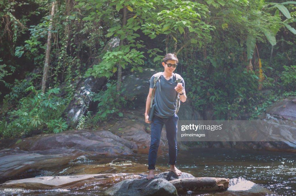 Hiker ryggsäck och bärbara datorn med telefon på vattenfall i skogen. : Bildbanksbilder
