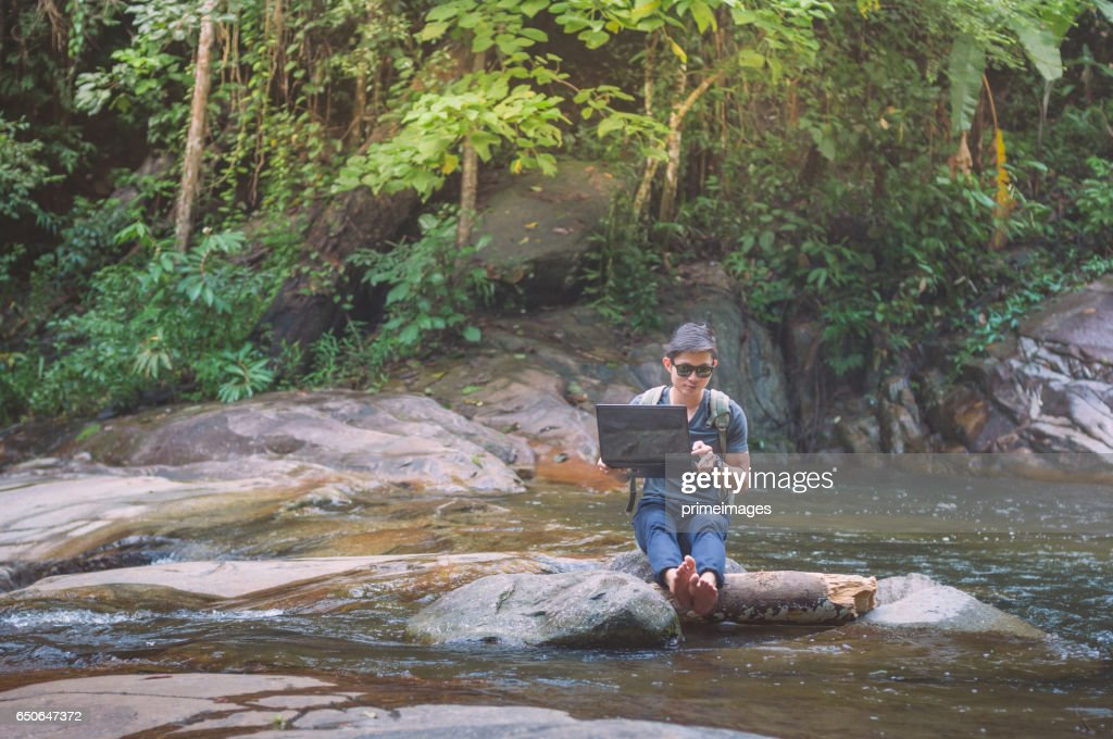 Wanderer mit Rucksack und Laptop und Handy am Wasserfall im Wald. : Stock-Foto