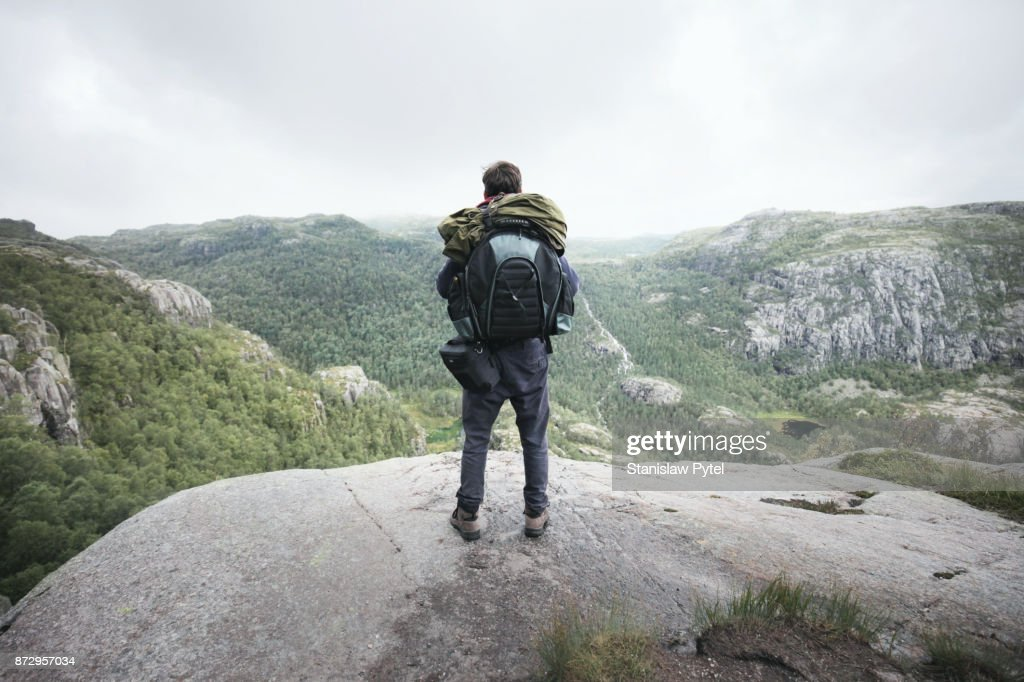Hiker with backpack looking at majestic mountains with forest : Stock Photo
