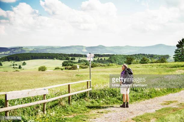 hiker with backpack, looking at signpost - hesse germany stock pictures, royalty-free photos & images