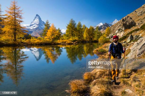 hiker with backpack on autumn mountain landscape with matterhorn peak background - zermatt stock pictures, royalty-free photos & images