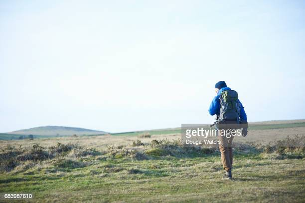 hiker with backpack walking over barren moorland. - blue jacket stock pictures, royalty-free photos & images