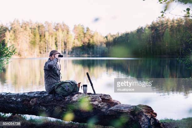 Hiker With Binoculars By The Lake During Sunset