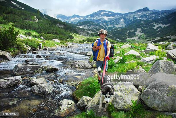 Hiker with husky dog in mountains